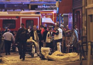Police officers and rescue workers gather around a victim outside in the 10th district of Paris, Friday, Nov. 13, 2015.  At least 35 people were killed Friday in shootings and explosions around Paris, many of them in a popular concert hall where patrons were taken hostage, police and medical officials said. (AP Photo/Jacques Brinon)