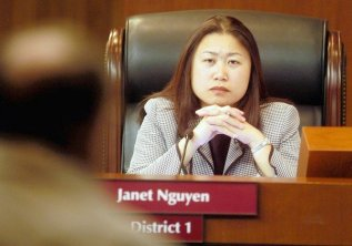 "Martin, Marc –– – 135389.ME.0318.norby.MM – Orange County supervisor Janet Nguyen listen to a public comment as county supervisors voted Tuesday to rename 11 county departments and agencies with the ""OC"" brand made famous by the now–defunct television show of the same name."