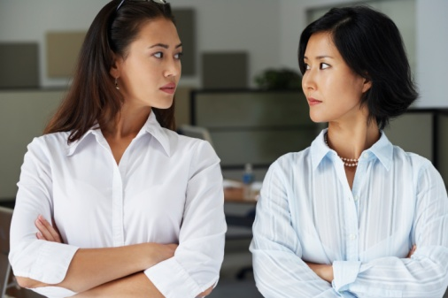 Two Asian businesswomen looking at each other in office