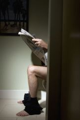 Mature man reading newspaper on toilet, side view, low section
