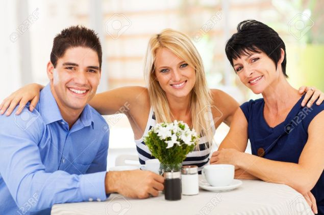 17452582-happy-young-man-with-wife-and-mother-in-law-in-cafe-Stock-Photo