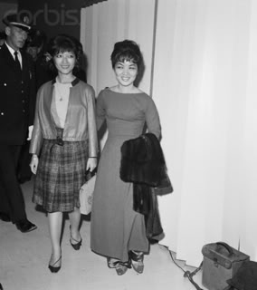 """06 Oct 1963 --- Mme. Ngo Dinh Nhu, sister-in-law of South Vietnamese President Ngo Dinh Diem, arrives at Idlewood Airport here late October 7th to begin a three-week visit to the United Staes. At left is her 16 year-old daughter, Le Thuy. South Viet Nam's controversial First lady said she came to this country """"to see you and try to understand why we can't get along better."""" --- Image by © Bettmann/CORBIS"""