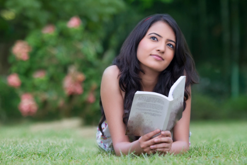 Thoughtful Indian woman with book relaxing in park