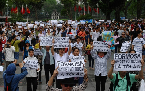 Vietnamese protesters demonstrate against Taiwanese conglomerate Formosa during a rally in downtown Hanoi on May 1, 2016.  Around a thousand people poured into Vietnam's two major cities Hanoi and Ho Chi Minh City to protest against Taiwan's Formosa, which operates a steel plant which they claim is causing mass fish kills due to pollution in Vietnam's central coast. / AFP PHOTO / HOANG DINH NAM
