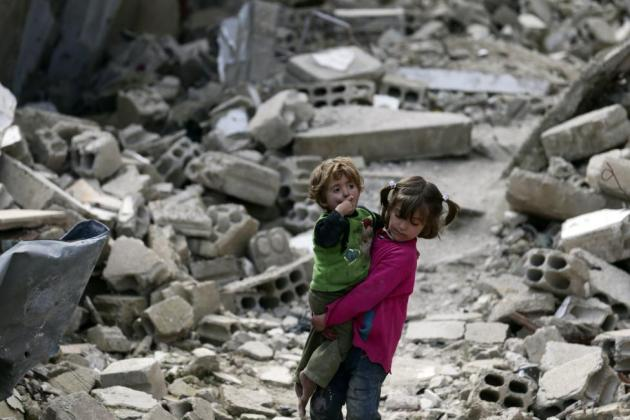 Local resident Israa holds her sister Boutol as they make their way through rubble of damaged buildings in the Douma neighborhood of Damascus, March 4, 2015. REUTERS/Bassam Khabieh
