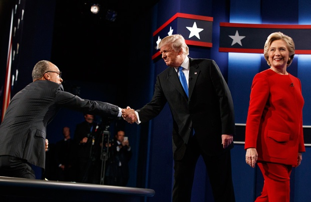 Republican presidential candidate Donald Trump, center, shakes hands with moderator Lester Holt, left, as Democratic presidential candidate Hillary Clinton walks to her lectern during the first presidential debate at Hofstra University, Monday, Sept. 26, 2016, in Hempstead, N.Y. (Evan Vucci/AP/CP)