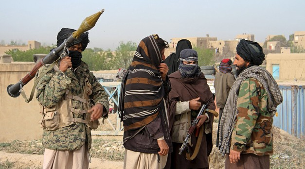 Members of the Taliban gather at the site of the execution of three men accused of murdering a couple during a robbery in Ghazni Province April 18, 2015.  The Taliban announced the execution of the three men accused of murdering a couple during a robbery, saying they had been tried by an Islamic court. The killing was carried out in front of a crowd by Taliban fighters who fired at the men with AK-47s, according to a Reuters witness. Footage seen by Reuters show the men were made to sit on the ground with their eyes blindfolded and their hands tied at the time of their execution. REUTERS/Stringer - RTR4XU49