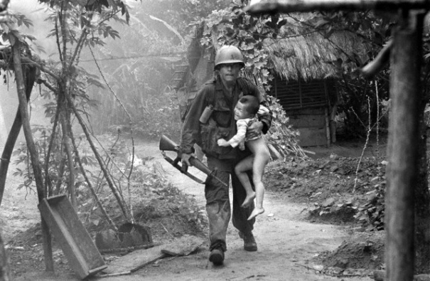 22 Aug 1966, Vietnam --- A U.S. infantryman from A Company, 1st Battalion, 16th Infantry  carries a crying child from Cam Xe village after dropping a phosphorous grenade into a bunker cleared of civilians during an operation near the Michelin rubber plantation northwest of Saigon, August 22, 1966. A platoon of the 1st Infantry Division raided the village, looking for snipers that had inflicted casualties on the platoon. GIs rushed about 40 civilians out of the village before artillery bombardment ensued. (AP Photo/Horst Faas) | Location: Cam Xe, Vietnam.  --- Image by © Horst Faas/AP/Corbis