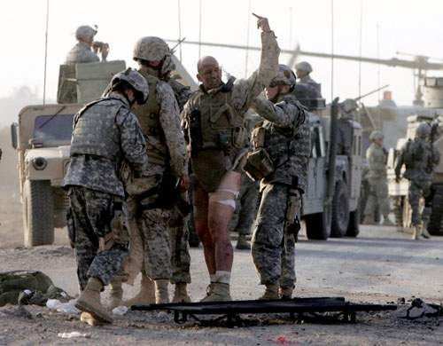 mnw15bombs1 MUST CREDIT: Jeff Bundy/The Omaha World-Herald Gunnery Sgt. Michael Burghardt signals his defiance after being struck by an IED Monday Sept. 19, 2005 near Ramadi, Iraq. The Marine refused to be carried away on a streacher and walked under his own power to a waiting medavac. Attending to the marine was Nebraska 167 CAV members Spc. John Adams (far left in front) and PFC. Darin Nelson of Fremont Neb. Burghardt is an EOD with the United States Marine Corps. (Staff photo by Jeff Bundy/the Omaha World-Herald) (mnw# 42p cm)