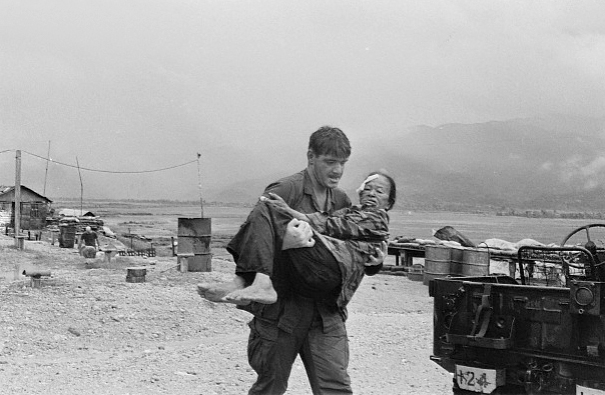 25 Oct 1968, Vietnam --- A US marine carries an injured woman to safety. --- Image by © Hulton-Deutsch Collection/CORBIS