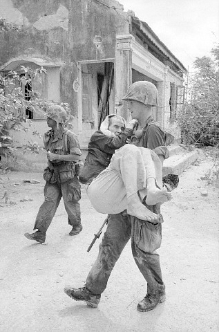 """10 Sep 1965, Qui Nhon, Vietnam --- Original caption: 9/10/1965-Qui Nhon, South Vietnam: While most of the men in a village, north of Qui Nhon, fled their homes as the US Marines marched in, some still remained. Here, Cpl. John Glover of Miami, FL, carries a sick old Vietnamese man to an aid station as a Marine buddy walks nearby looking for snipers, the """"unknown enemy"""", that constantly threatens the leathernecks in a village which was heavily infiltrated by the Viet Cong. (Original caption) --- Image by © Bettmann/CORBIS"""