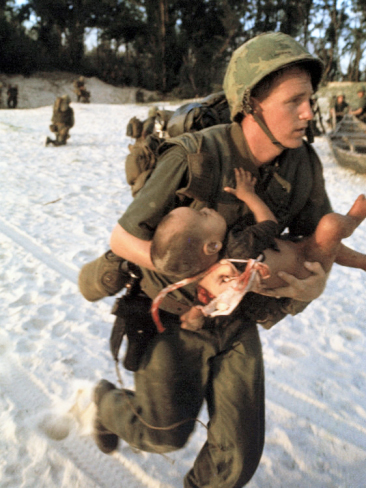 paul-schutzer-us-marine-medic-running-along-beach-with-injured-vietnamese-infant-under-fire-during-vietnam-war