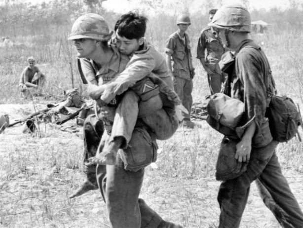 05 Mar 1966, Vietnam --- Pfc. John Stananback of East Paterson, N.J., carries a Viet Cong soldier on his back to a first aid station near Bau Bang, 30 miles north of Saigon, March 5, 1966. Soldiers of the U.S. 2nd Battalion, 28th Infantry fought off a multi-battalion Viet Cong attack, and found this man left behind, bloodied, barefoot and unarmed. (AP Photo/Horst Faas) | Location: Bau Bang, VIETNAM.  --- Image by © Horst Faas/AP/Corbis