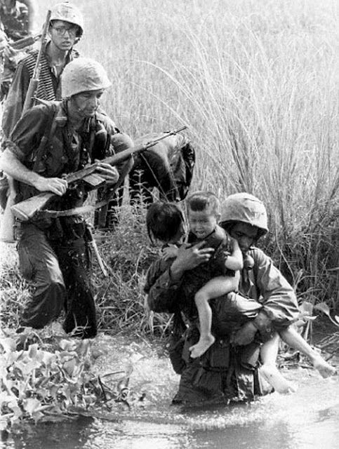 10 Sep 1965, Vietnam --- Original caption: 9/10/1965-Quinhon, South Vietnam:  The brutality and heartlessness of the war here can be seen in this photo of a marine carrying two, orphaned Vietnamese children across a swamp.  The US leathernecks swept through the area near this coastal city attempting to unearth Viet Cong Guerrillas. --- Image by © Bettmann/CORBIS