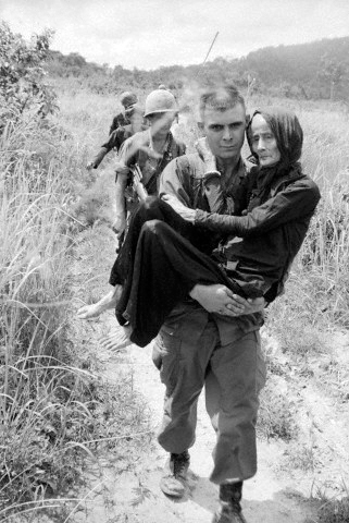 03 Aug 1965, Vietnam --- Original caption: 8/3/1965-Ba Ria, South Vietnam: An aged woman injured by a U.S.-Vietnamese air strike on a Buddist monastery 40 miles southeast of Saigon is carried to a hospital by airborne private Carl Champ of Furgitsville, West Virginia.  American and Vietnamese were carrying out joint operations against the Viet Cong in the area when the monastery was bombed. --- Image by © Bettmann/CORBIS