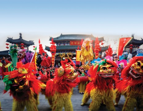 09 Feb 2013, Beijing, China --- epa03574640 A photo made with a tilt-shift lens shows performers in traditional lion costume posing for photographers on the eve of the New Year of the Snake at a park in Beijing, China, 09 February 2013. China's main annual holiday, the Spring Festival or Lunar New Year of the snake according to the traditional twelve year zodiac cycle, will begin on 10 February. EPA/DIEGO AZUBEL --- Image by © DIEGO AZUBEL/epa/Corbis