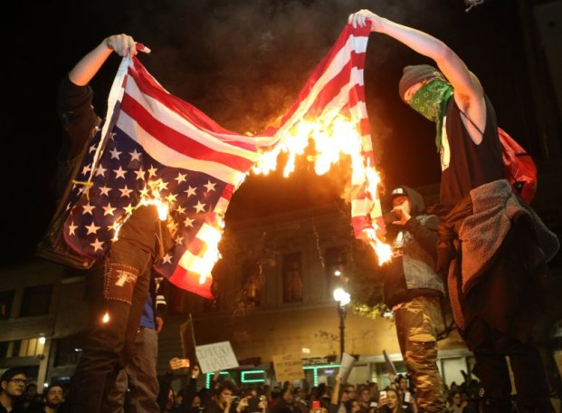 Protesters burn an American flag during a march along Broadway near 20th Street in demonstration against President-elect Donald Trump in Oakland, Calif., on Wednesday, Nov. 9, 2016. (Anda Chu/Bay Area News Group)