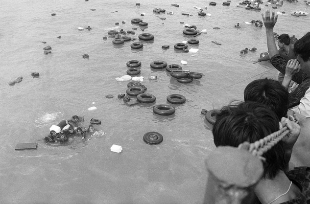 A cluster of South Vietnamese marines, some of whom unable to swim, hold onto inner tubes and empty plastic containers as buddies throw them a line to pull them aboard a navy LST off China Beach at Danang as they fled the port city in April of 1975. #