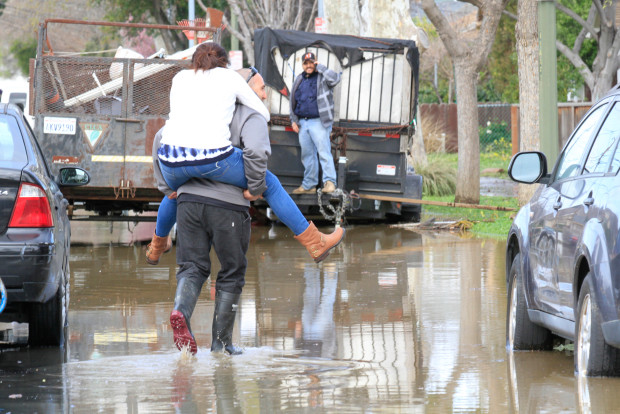 Residents of S. 20th Street wade through the flooded street as the water recedes in their neighborhood on Wednesday, Feb. 22, 2017 in San Jose, Calif.(Laura A. Oda/Bay Area News Group)