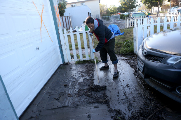 Resident Hieu Le cleans up after flooding damaged his home and many others along Rock Springs Drive in San Jose, Calif., on Thursday, Feb. 23, 2017. (Anda Chu/Bay Area News Group)