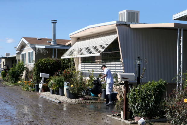 Duy Nguyen cleans up outside the home he shares with his parents at the South Bay Mobile Home Park following recent flooding in San Jose, Calif., on Thursday, Feb. 23, 2017. (Anda Chu/Bay Area News Group)